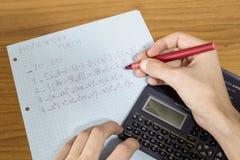Een student doet wiskundethuiswerk met een calculator en een pen royalty-vrije stock foto's