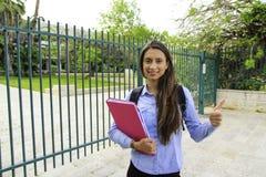 Een student houdt een bindmiddel met een glimlach bij de ingang aan de universiteit royalty-vrije stock foto's