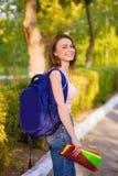 Een studente met een rugzak in park Stock Afbeelding