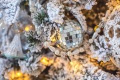 Een stuk speelgoed in de vorm van een Nieuwjaar` s bal op een verfraaide Kerstboom Stock Foto's