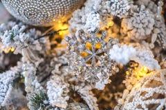 Een stuk speelgoed in de vorm van een sneeuwvlok op een verfraaide Kerstboom Stock Fotografie