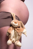 Een stuk speelgoed hangin door een zwangere buik Stock Fotografie