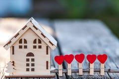 Een stuk speelgoed huis met een omheining van harten stock foto's