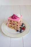 Een stuk van aardbei-romige die cake, met een roze die room wordt behandeld en met heemst en bessen wordt verfraaid Royalty-vrije Stock Foto