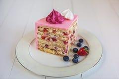 Een stuk van aardbei-romige die cake, met een roze die room wordt behandeld en met heemst en bessen wordt verfraaid Stock Foto