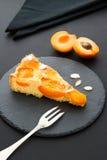 Een stuk van abrikoos scherp met amandelstroken op een zwarte lei Stock Afbeelding