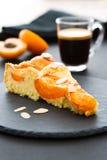 Een stuk van abrikozencake met amandelstroken op een zwarte ronde lei Stock Foto