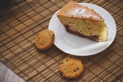 Een stuk van biscuitgebak op een ronde witte plaat met chocolade BIB stock afbeelding
