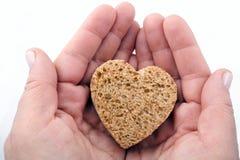 Een stuk van brood bood met liefde aan stock foto's
