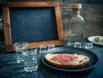 Een stuk van brood met plak van varkensvlees en schoten van wodka op houten achtergrond stock fotografie