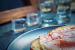 Een stuk van brood met plak van varkensvlees en schoten van wodka op houten achtergrond royalty-vrije stock fotografie