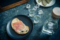 Een stuk van brood met plak van varkensvlees en schoten van wodka op houten achtergrond royalty-vrije stock foto