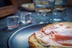 Een stuk van brood met plak van varkensvlees en schoten van wodka op houten achtergrond stock foto's
