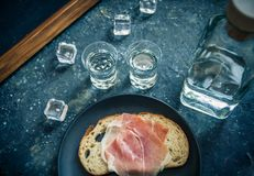 Een stuk van brood met plak van varkensvlees en schoten van wodka op houten achtergrond royalty-vrije stock foto's