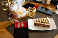 Een stuk van cake, een milkshake in een glas, een theepot, kop thee?n en bestek op een lijst in een koffie royalty-vrije stock foto's