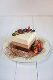Een stuk van een moussecake drie chocolade bevindt zich op een plaat die, met geraspte chocolade wordt bestrooid, en verfraaide m Stock Foto