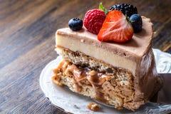 Een stuk van eigengemaakte cake met macaron en vers fruit, bessen op een houten achtergrond royalty-vrije stock afbeelding