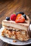 Een stuk van eigengemaakte cake met macaron en vers fruit, bessen op een houten achtergrond royalty-vrije stock afbeeldingen