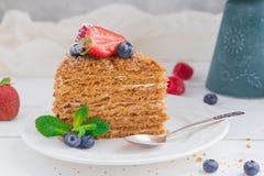 Een stuk van eigengemaakte honingscake met aardbeien, bosbessen en frambozen op lichte achtergrond Royalty-vrije Stock Afbeeldingen