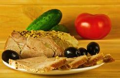 Een stuk van geroosterd vlees met olijven op een witte plaat Stock Foto