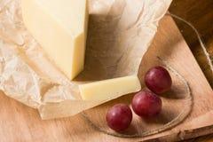 Een stuk van harde die kaas in document en rode druiven op de keukenlijst wordt verpakt royalty-vrije stock afbeeldingen