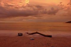 Een stuk van hout op het zand van het strand van Kuta Bali bij schemer stock foto's