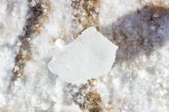 Een stuk van ijs legt op de sneeuw Stock Afbeelding
