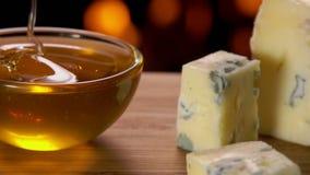 Een stuk van kaas met schimmel wordt ondergedompeld in een kom met honing stock video