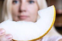 Een stuk van meloen dichte omhooggaand in de hand van een vage blonde vrouw royalty-vrije stock afbeelding