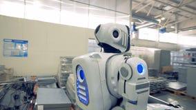 Een stuk van metaalmontage wordt gedragen door androïde bij een fabriek 4K stock videobeelden