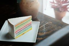 Een stuk van Regenboogcake en de koffie van ijsmocha op donkere houten lijst Stock Afbeelding