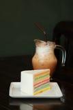 Een stuk van Regenboogcake en de koffie van ijsmocha op donkere houten lijst Stock Afbeeldingen