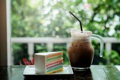 Een stuk van Regenboogcake en de koffie van ijsmocha op donkere houten lijst Stock Foto's