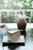 Een stuk van Regenboogcake en de koffie van ijsmocha op donkere houten lijst Royalty-vrije Stock Foto