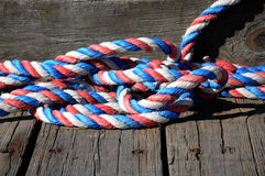 Een stuk van rode, witte en blauwe kabel rolde op een dok stock foto
