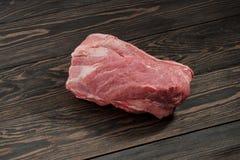 Een stuk van ruwe varkensvleeshals Varkensvleeshaasbiefstuk op papier op een donkere achtergrond Stock Foto's