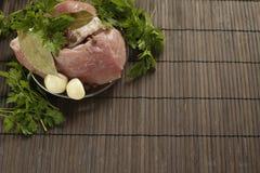Een stuk van vers vlees op een plaat met knoflook, peterselie, lautre doorbladert en peper op een houten achtergrond Stock Foto's