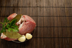 Een stuk van vers vlees op een plaat met knoflook, peterselie, lautre doorbladert en peper op een houten achtergrond Royalty-vrije Stock Foto's