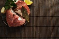 Een stuk van vers vlees op een plaat met knoflook, peterselie, lautre doorbladert en peper op een houten achtergrond Stock Foto
