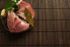 Een stuk van vers vlees op een plaat met knoflook, peterselie, lautre doorbladert en peper op een houten achtergrond Stock Fotografie