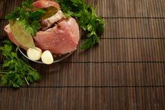 Een stuk van vers vlees op een plaat met knoflook, peterselie, lautre doorbladert en peper op een houten achtergrond Royalty-vrije Stock Fotografie