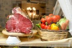 Een stuk van vlees op de tribune Groententomaten, groene paprika's, kool, wortelen in een mand stock fotografie