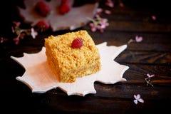 Een stuk van zoete honingscake op een plaat in de vorm van een esdoornblad cakes Stock Afbeelding