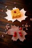 Een stuk van zoete honingscake op een plaat in de vorm van een esdoornblad cakes Royalty-vrije Stock Afbeelding