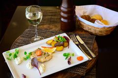 Een stuk vissen met groenten en gebraden aardappels op een plaat stock fotografie