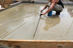 Een stukadoor concrete arbeider aan het vloerwerk Stock Foto