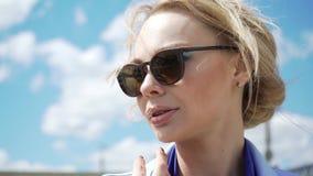 Een stunningly mooi jong blonde in vliegeniers` s zonnebril en backlit van de zon stock videobeelden