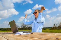 Een succesvolle werkende vrouw met omhoog laptop en wapens royalty-vrije stock foto's
