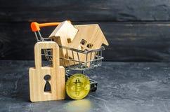Een supermarktkar met huizen en bitcoin en een hangslot de groeiwaarde Bitcoin en de betrouwbaarheid van investeringen op lange t stock foto's