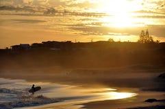 Een surfersilhouet tegen een zonsondergangachtergrond stock afbeeldingen